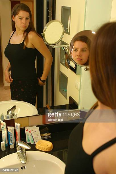 A young woman lokking at herself in the mirror