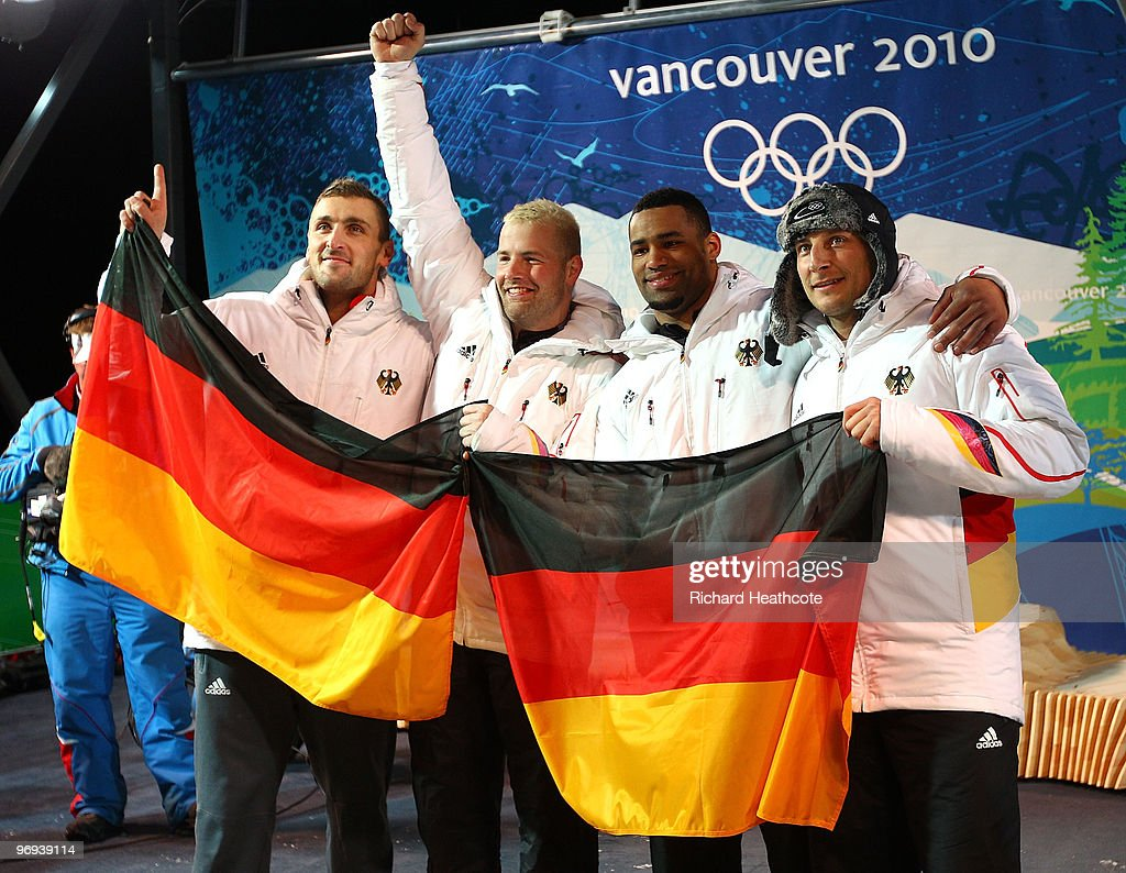 Germany 1 with <a gi-track='captionPersonalityLinkClicked' href=/galleries/search?phrase=Andre+Lange&family=editorial&specificpeople=242817 ng-click='$event.stopPropagation()'>Andre Lange</a> (2ndL) and <a gi-track='captionPersonalityLinkClicked' href=/galleries/search?phrase=Kevin+Kuske&family=editorial&specificpeople=780181 ng-click='$event.stopPropagation()'>Kevin Kuske</a> (L) celebrate their gold medal with silver medalists Germany 2 Richard Adjei and Thomas Florschuetz (R) after the Two-Man Bobsleigh Heat 4 on day 10 of the 2010 Vancouver Winter Olympics at the Whistler Sliding Centre on February 21, 2010 in Whistler, Canada.