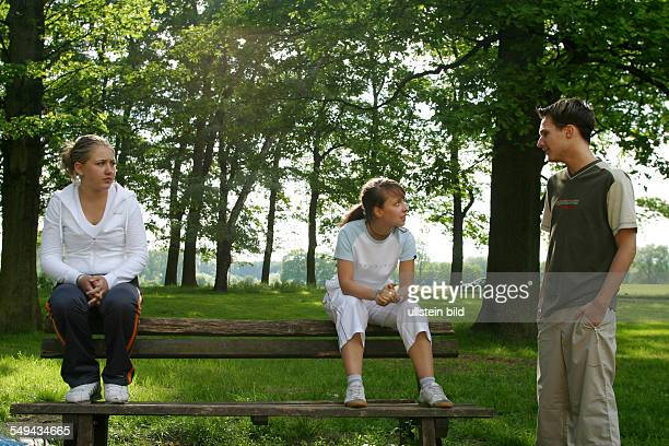 Free time Three young persons talking in a park the girls are sitting on a wooden bench