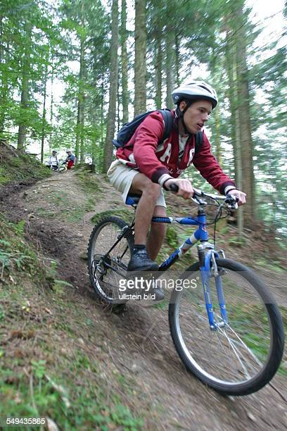A young man riding with his mountainbike through the wood