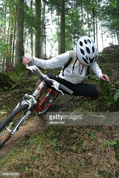 A young woman falling off her mountainbike while she was riding through the wood