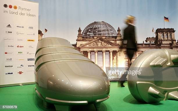 A fair hostess walks past giant mockups of football shoes in front of a poster of Berlin's Reichstag building at the booth of the initiative 'Germany...