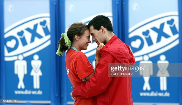 A pilgrims couple kisses in front of toilets during the World Youth Day 20 August 2005 at the Marienfeld near Kerpen before pope Benedict XVI will...