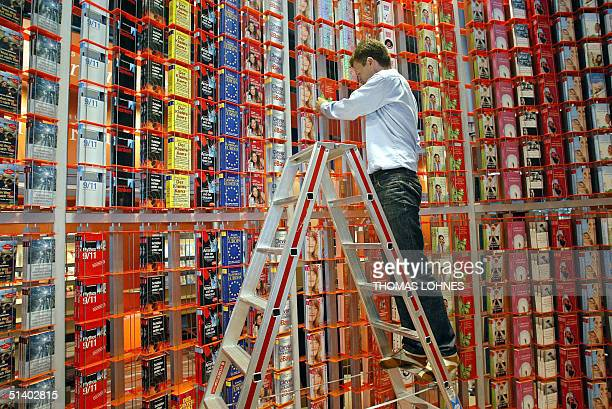 A Publisher's associate stands on a ladder as he fills a huge shelf with books 05 October 2004 ahead of the 56th edition of the Frankfurt Book Fair...