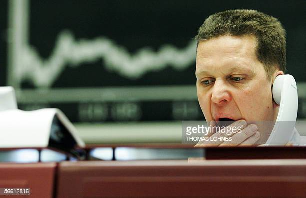 A trader sitting in front of a chart displaying German share index DAX gestures as he speaks on the phone 18 January 2006 at the stock exchange in...