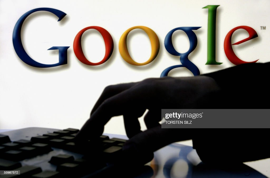 A woman works on her computer as on the wall behind is seen the logo of web search engine Google at Frankfurt's international book fair on 23 October...