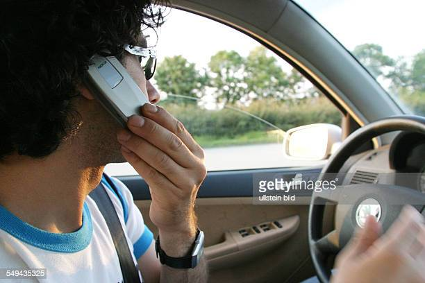 A young man phoning with his mobile phone while he is driving a car