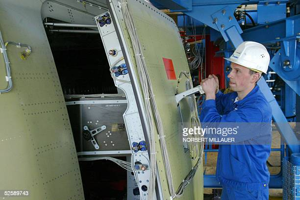 An aircraft mechanic checks the door of an Airbus A380 at a new test site of the IABG company for the Airbus A380 in Dresden 05 April 2005 During the...
