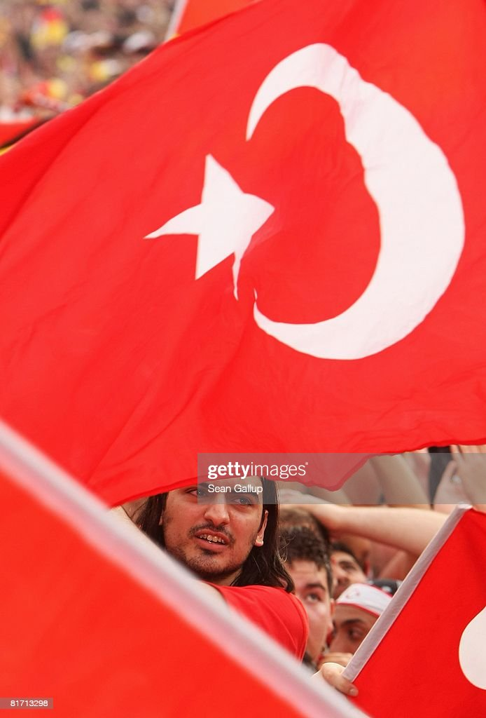 Germany and Turkey football fans wave their national flags in front of a largescreen monitor at the Fan Mile public viewing area in front of the...