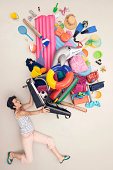 Germany, Artificial scene with woman opening baggage full of beach toys