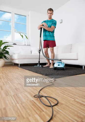 germany augsburg man cleaning apartment with vacuum