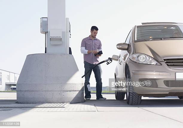 Germany, Augsburg, Young man at petrol pump with car