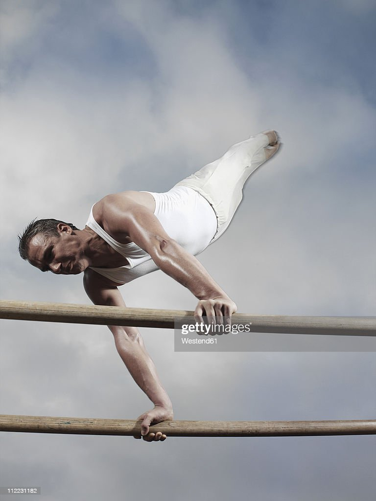 Germany, Augsburg, Young man balancing on parallel bars