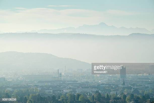 Germany, Baden Wuerttemberg, Constance district, Cityscape Singen at Hohentwiel in the early-morning haze, in the background Swiss Alps with Saentis