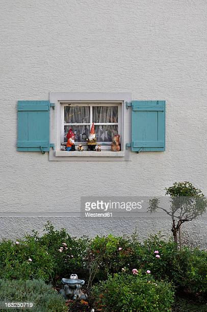 Germany, Baden Wuerttemberg, Window with shutter and garden gnomes