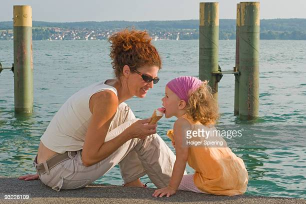 Germany, Baden-Wuerttemberg, Lake Constance, Mother feeding ice cream to daughter (4-5)