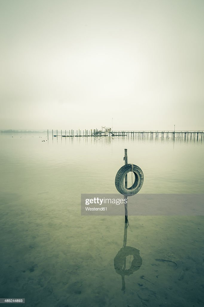 Germany, Baden-Wuerttemberg, Car tyre in water and jetty at Iznang