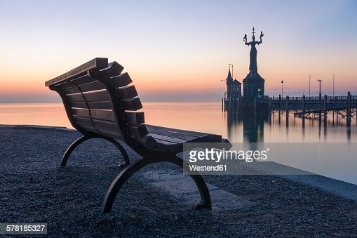 Germany, Baden-Wuerttemberg, Constance, Lake Constance, empty bench and harbour entrance with Imperia Statue at twilight