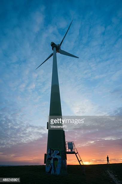 Germany, Baden-Wuerttemberg, Korntal-Muenchingen, Gruener Heiner, one man standing near windmill at sunset