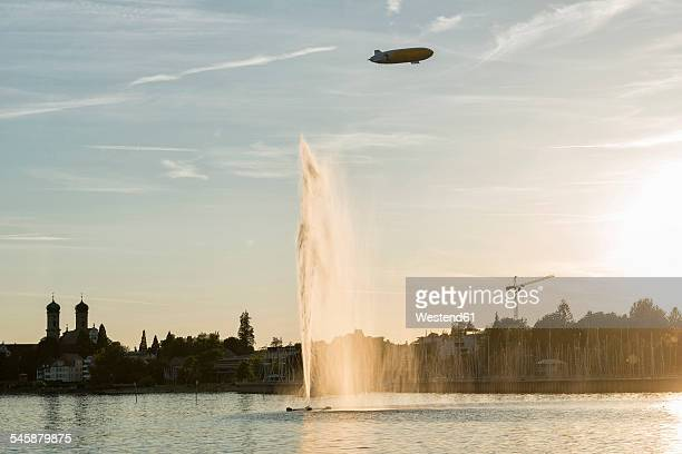 Germany, Baden-Wuerttemberg, Lake Constance, Friedrichshafen, fountain and zeppelin at sunset