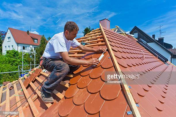 Germany, Baden-Wuerttemberg, Stuttgart, Mid adult man measuring roof tile