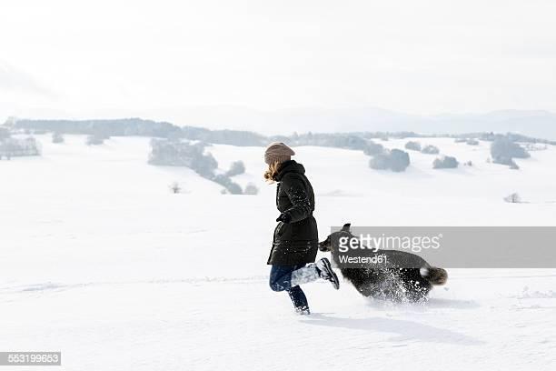 Germany, Baden-Wuerttemberg, Waldshut-Tiengen, woman and dog running in snow