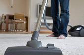 Germany, Baden-Wurttemberg, Stuttgart, Man vacuuming carpet, low section