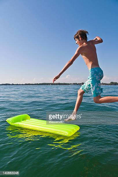 Germany, Baden-Wurttemberg, Teenage boy jumping in Lake Constance