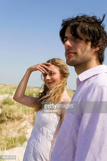 Germany, Baltic sea, couple standing in sand dunes, looking away