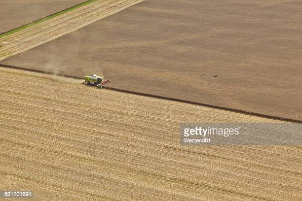 Germany, Bavaria, aerial view of combine harvester on cornfield