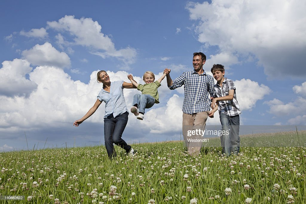Germany, Bavaria, Altenthann, Family playing together in meadow : Stock Photo