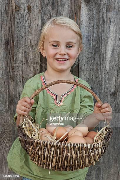 Germany, Bavaria, Altenthann, Girl holding basket of eggs, smiling, portrait