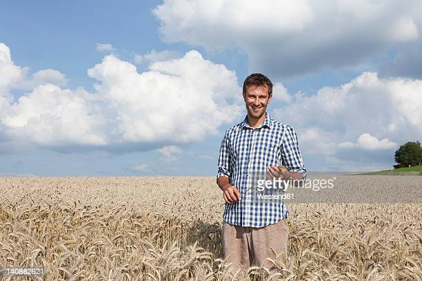 Germany, Bavaria, Altenthann, Man standing in wheat field, smiling, portrait