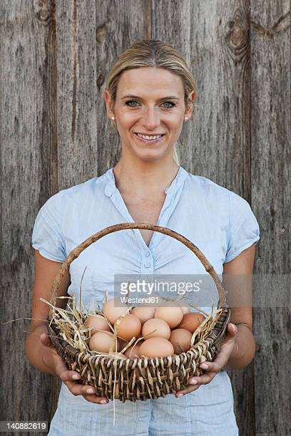 Germany, Bavaria, Altenthann, Woman Holding basket of eggs, smiling, portrait