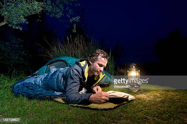 Germany, Bavaria, Ammersee, Man reading book near lakeshore while camping at night