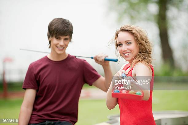 Germany, Bavaria, Ammersee, Teenage couple (16-17), boy holding golf club, smiling, portrait