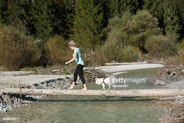 Germany, Bavaria, Bavarian Alps, Vorderriss, young woman and little dog are balancing on tree trunk to cross a river