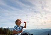 Germany, Bavaria, Boy (4-5 Years) blowing soap bubbles