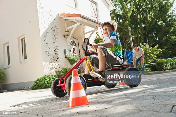 Germany, Bavaria, Boy driving pedal go kart with parents in background