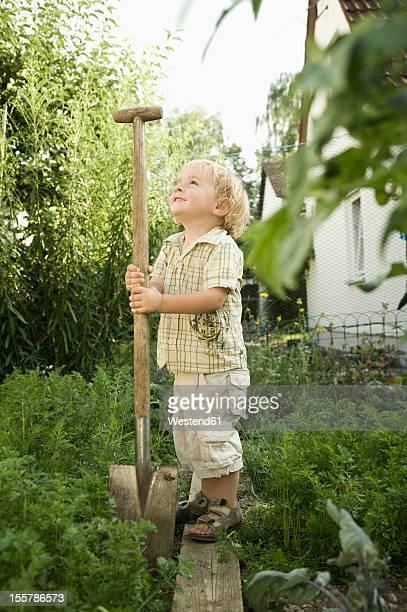 Germany, Bavaria, Boy holding shovel in garden