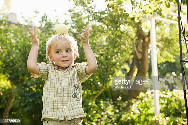 Germany, Bavaria, Boy playing with apple on top of head