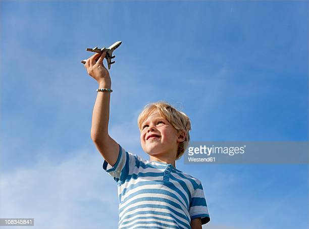 Germany, Bavaria, Boy (4-5 Years) playing with toy airplane