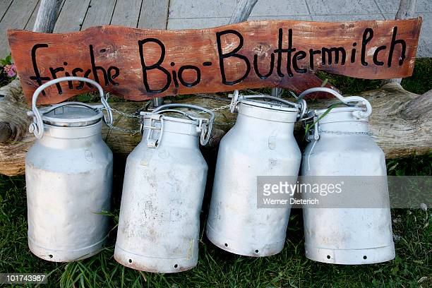 Germany, Bavaria, Chiemgau, Row of milk churns in front of wooden sign