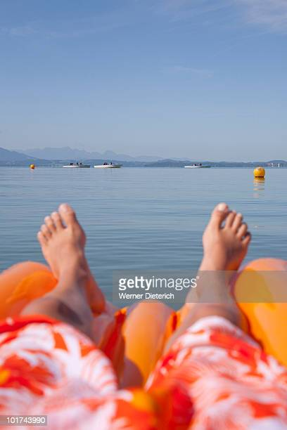 Germany, Bavaria, Chiemsee, Child lying on air mattress, low section