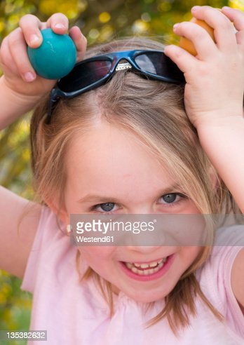 Germany, Bavaria, Close up of girl joking with easter eggs, smiling, portrait : Stock Photo