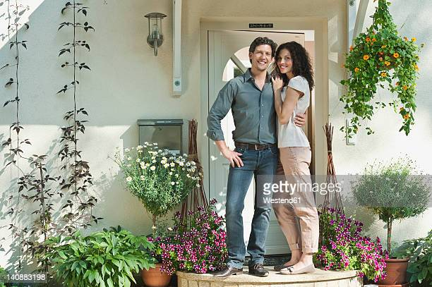 Germany, Bavaria, Couple at entrance of house, smiling, portrait