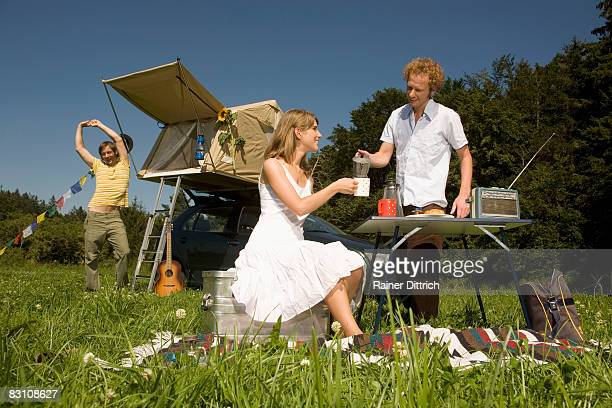 Germany, Bavaria, couple having break fast in meadow, man standing by camping tent in background