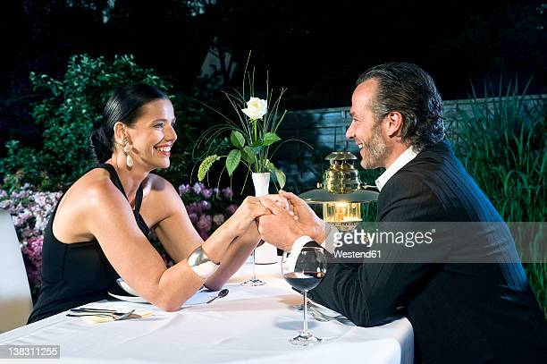 Germany, Bavaria, Couple romancing while candlelight dinner