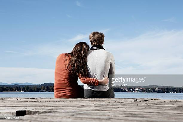 Germany, Bavaria, Couple sitting on jetty at Lake Starnberg