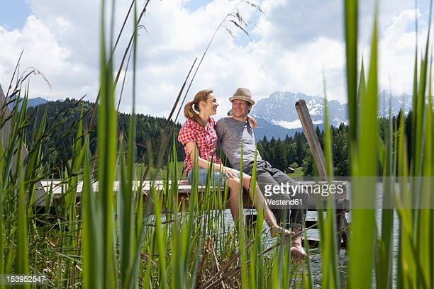 Germany, Bavaria, Couple sitting on jetty, smiling